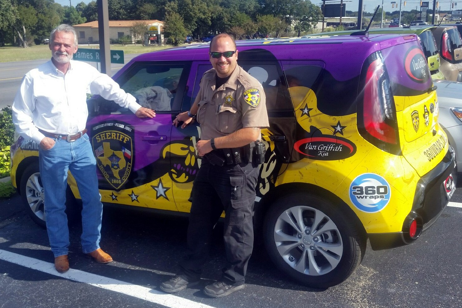 two smiling men next to a purple and gold car